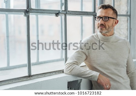 Thoughtful man wearing glasses standing relaxing against a windowsill staring out of a window with a serious expression with copy space