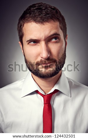 thoughtful man with distrust looking up over grey background