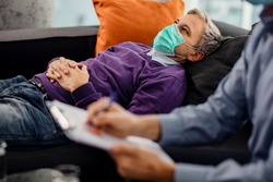 Thoughtful man with face mask lying down on psychiatrist's couch during a therapy session with mental health professional.