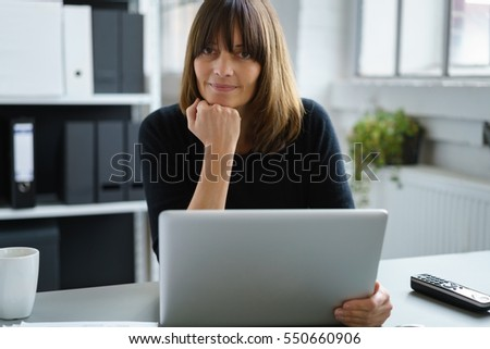 Stock Photo Thoughtful mature business woman sat at desk in office with laptop resting chin on hand, folders in background.