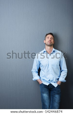 Thoughtful mature businessman with hands in pockets looking up against blue wall