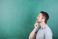 Thoughtful mature male teacher with hand on chin against blank blackboard