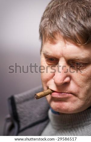 Thoughtful mature man smoking cigar