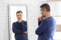 Thoughtful mature man standing near mirror at home