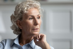 Thoughtful mature 60s woman look in distance thinking or pondering over life problem, pensive senior 70s grandmother lost in thoughts, feel loneliness solitude in retirement years, missing at home