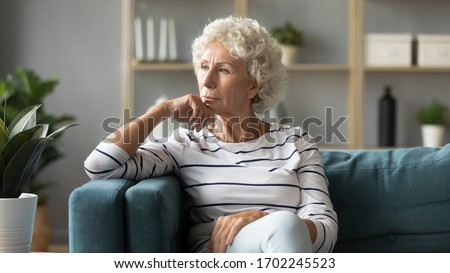 Thoughtful mature woman sitting on couch at home alone, dreaming and planning, serious pensive older senior female looking into distance, in window in living room, thinking about problems