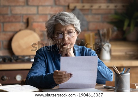 Thoughtful middle aged 60s woman in eyeglasses reading paper letter carefully. Pensive focused older mature retired lady looking at correspondence sheet. considering bank notification at home. Photo stock ©