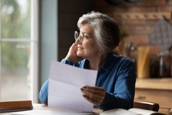 Thoughtful middle aged senior woman in eyeglasses holding paper document in hands, looking in distance. Pensive smiling older mature lady feeling pleased after reading correspondence letter at home.