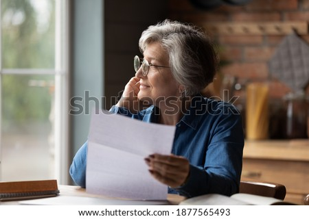 Thoughtful middle aged senior woman in eyeglasses holding paper document in hands, looking in distance. Pensive smiling older mature lady feeling pleased after reading correspondence letter at home. Foto stock ©