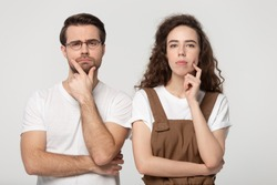 Thoughtful millennial guy in eyewear standing together with young doubtful girl, folding hands, touching chins, thinking over job offer or sale propose, isolated on grey white studio background.