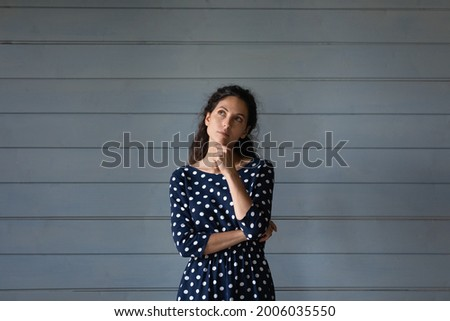 Thoughtful millennial Hispanic woman in spotted dress touching chin in deep thoughts, looking away, thinking of choice, offer, opportunities, future success, making decision. Head shot portrait Photo stock ©