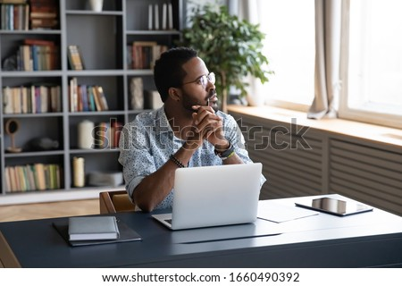 Thoughtful mixed race businessman sitting at table with computer, looking away. Distracted from study job young african american man lost in thoughts, thinking of difficult decision at home office.