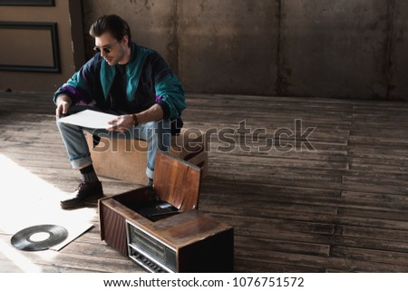 thoughtful nostalgic man in vintage windcheater with vinyl record player #1076751572