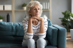 Thoughtful old 60s lady sit on couch in living room look in distance remembering missing past, pensive elderly female relax on sofa at home or retirement house feel lonely thinking pondering