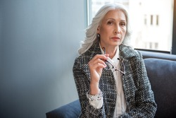 Thoughtful old woman is posing on couch