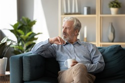 Thoughtful older man sitting on couch at home alone, holding cup of tea or coffee, feeling lonely and sad, unhappy depressed mature male looking into distance, thinking about problems