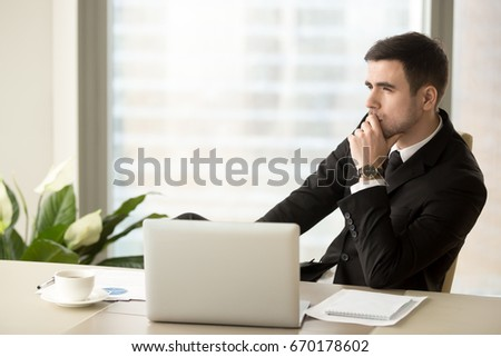 Thoughtful pensive businessman deep in thoughts looking away sitting near laptop at workplace, successful entrepreneur thinking over new ways to improve business, future perspectives, managing risks