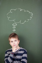 Thoughtful preadolescent student standing against chalkboard with thought bubble drawn on it