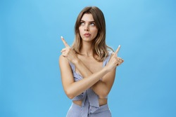 Thoughtful questioned attractive female coworker trying make choice facing hard decision crossing hands against chest pointing left and right looking focused while thinking over blue background