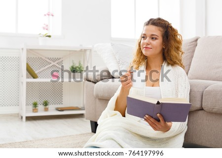 Thoughtful redhead student girl reading book. Young woman studying at home, sitting on floor, wrapped up in white blanket, copy space