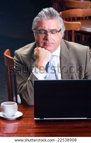 thoughtful senior business man sitting by his laptop and thinking
