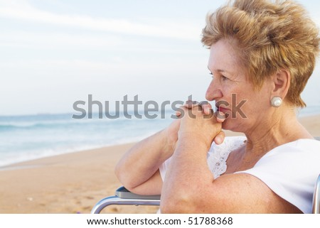 thoughtful senior disabled woman sitting on wheelchair on beach