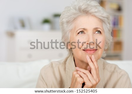 Thoughtful senior lady sitting at home with her fingers to her chin reminiscing and recalling fond memories, close up portrait