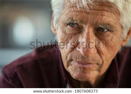 Thoughtful senior man sitting on couch looking away with copy space. Depressed sad man thinking at home. Elderly pensive senior suffering from alzheimer disease. Photo stock ©