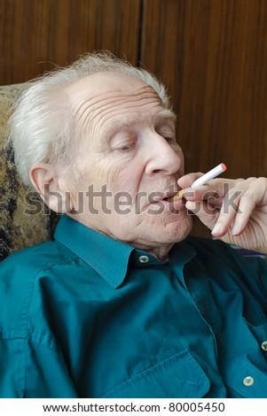 thoughtful senior man smoking electronic cigarette - stock photo