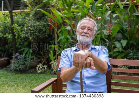Thoughtful senior old caucasian man holding cane sitting on bench in garden