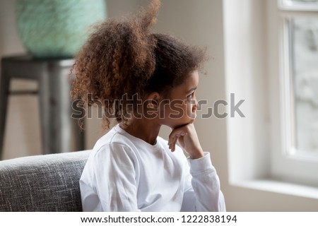 Thoughtful serious African American preschooler girl looking in window, pensive child sitting at home, hold hands under chin, dreaming, looking in distance, feeling boredom, having questions