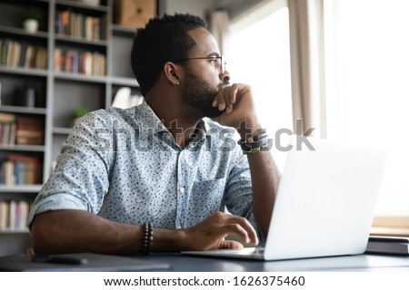 Thoughtful serious african professional business man sit with laptop thinking of difficult project challenge looking for problem solution searching creative ideas lost in thoughts at home office desk ストックフォト ©