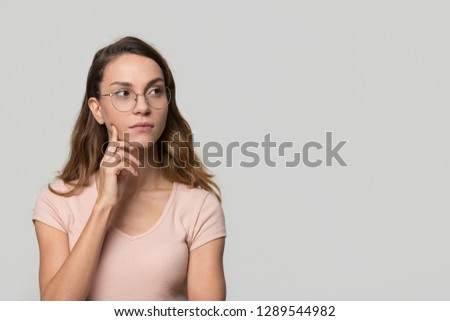 Thoughtful serious doubtful young woman with unsure face looking aside at copy free space for text feeling uncertain  thinking considering making decision isolated on white blank studio background