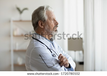 Thoughtful serious senior doctor looking through window lost in thoughts. Worried pensive old physician thinking of healthcare question, concerned of challenge, feels anxious makes difficult decision.
