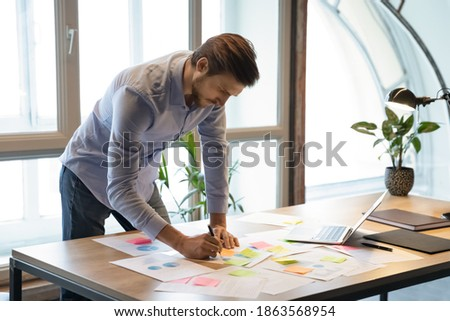 Thoughtful serious young businessman employee standing at desk focused on paperwork, making changes correcting mistakes in marketing plan by hand, analyzing client customer demands using infographics
