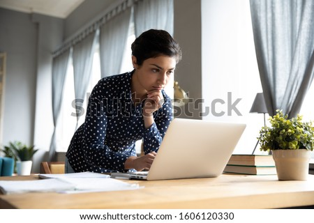 Thoughtful serious young indian ethnic woman student freelancer working studying on laptop computer looking at pc screen focused on thinking solving online problem doing research at home office desk.