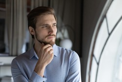 Thoughtful serious young man leader ceo executive looking at office window at workday visualizing business opportunities, dreaming of new achievements, creating personal ambitious strategy of success