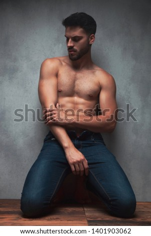 Thoughtful shirtless young man looking down and rubbing his hand while kneeing and leaning on gray studio background