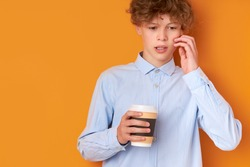 thoughtful sleepy boy has no enough sleep, need sleep in the morning before going at school, hold cup of coffee in hands, looks down. orange background