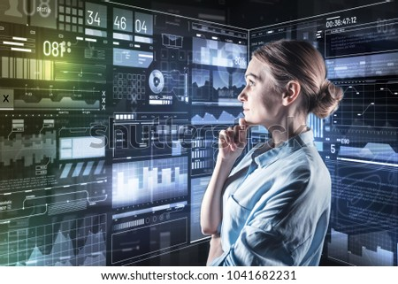 Thoughtful specialist. Clever young experienced programmer standing with her hand touching her chin and thoughtfully looking at the modern transparent screen #1041682231