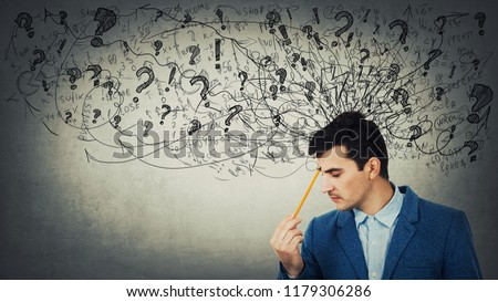 Thoughtful stressed young man with a mess in his head closed eyes pointing pencil to forehead. Anxiety and headache feeling.