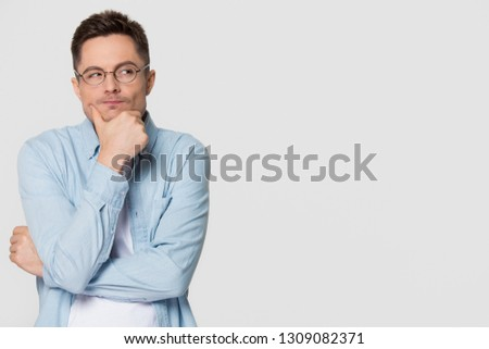 Thoughtful suspicious young man looking aside at copy space feeling skeptic doubtful, distrustful sly cunning guy thinking holding hand on chin isolated on grey white studio background