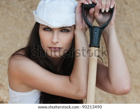 thoughtful tired beautiful woman leaning shovel white
