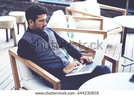Thoughtful wealthy businessman work on-line on net-book while sits at modern restaurant terrace, young intelligent rich man connecting to wireless via laptop computer during work break in coffee shop #644230858