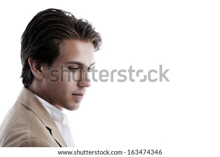 Thoughtful, wistful handsome young man in a jacket staring downwards with a serious expression, side view head and shoulder portrait on white with copyspace.