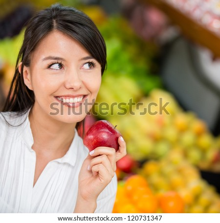 Thoughtful woman buying groceries at the supermarket - stock photo