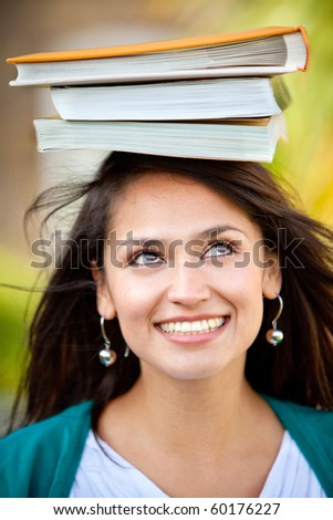 Thoughtful woman carrying books on her head and trying to balance them