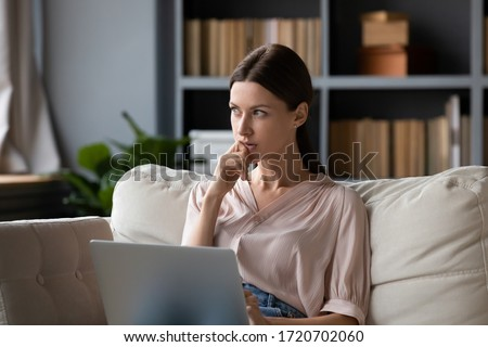 Thoughtful woman holding laptop on laps, pondering ideas or tasks, sitting on couch at home, dreamy young female touching chin and looking in distance, lost in thoughts, waiting for message