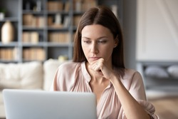 Thoughtful woman looking at laptop screen, pondering project, working online at home, sitting at desk, pensive young female touching chin, reading email, financial report, making decision