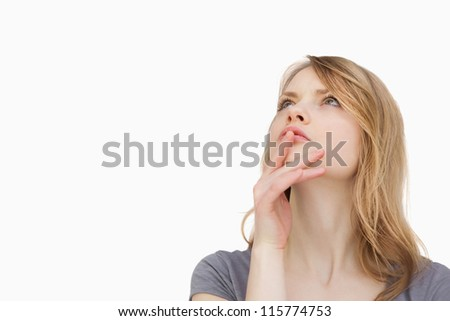 Thoughtful woman looking up against a white background